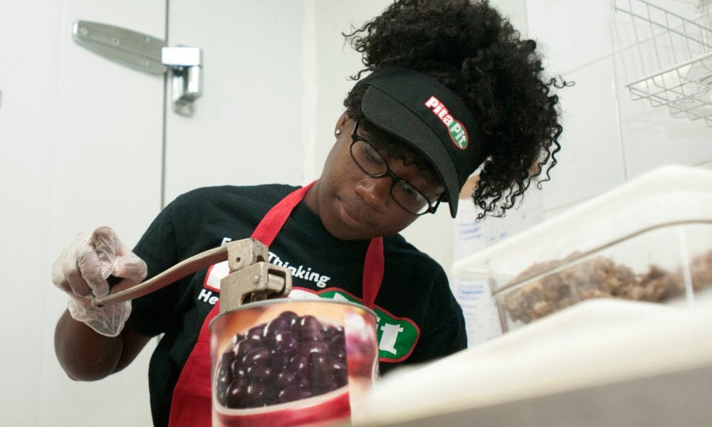 <p>Elementary education junior Kayla Jackson opens a can of olives on Sept. 23, 2015, at Pita Pit, 219 E. Grand River Ave., in East Lansing. Kayla stocked the back room and provided replacements when certain ingredients ran out during her shift. Kennedy Thatch/The State News</p>