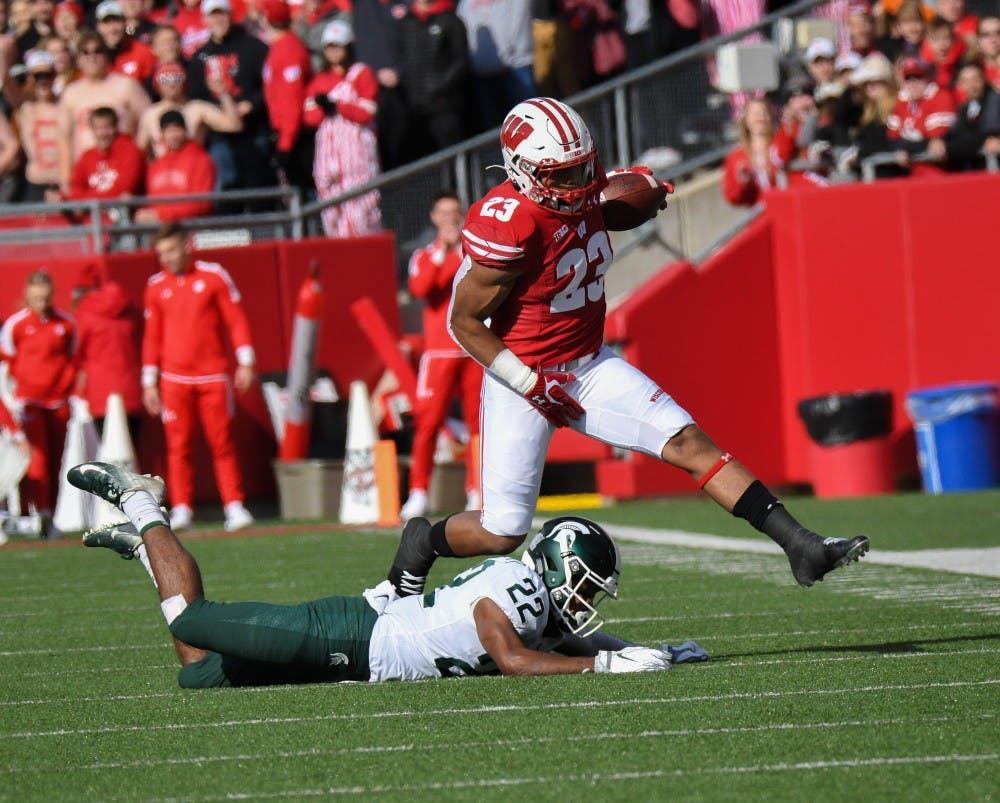 Wisconsin junior running back Jonathan Taylor (23) vaults over junior cornerback Josiah Scott (22) during the game against Wisconsin at Camp Randall Stadium on October 12, 2019. The Spartans lost to the Badgers 38-0.