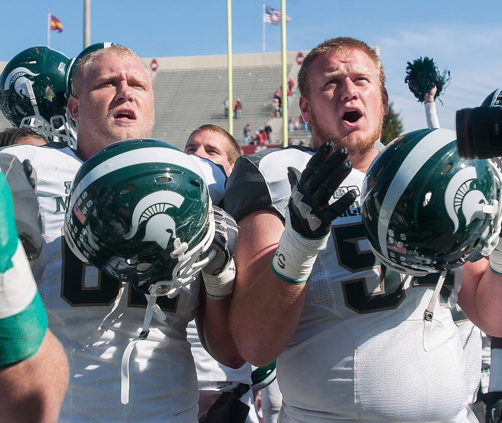 """<p>Senior offensive guard Chris McDonald and sophomore offensive guard Connor Kruse chant the <span class=""""caps"""">MSU</span> fight song after the game Saturday, Oct. 6, 2012, at Memorial Stadium in Bloomington, Ind. Despite trailing to Indiana at half-time, the Spartans were able to earn the 31-27 victory. Adam Toolin/The State News</p>"""
