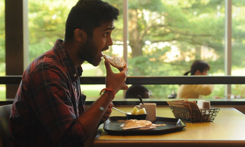 <p>Mechanical engineering senior Yash Kankaria eats a bagel on Sept. 20, 2015, inside the cafeteria in Case Hall. Kankaria has morning classes and usually eats breakfast before classes. &quot;It&#x27;s really crowded here, so it does get a bit frantic,&quot; Kankaria said.</p>