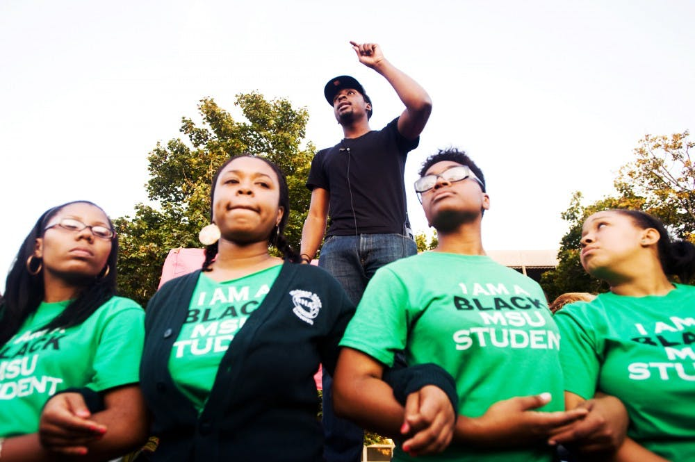 Social relations and policy senior Brandon Allen, center, speaks as social relations and policy sophomore Sirrita Darby, from left, social relations and policy junior Patricia Jackson, journalism junior Silver Moore and special education junior Genel Fowler link arms during the silent march and protest rally hosted by the Black Student Alliance and Iota Phi Theta fraternity on Thursday evening. The event was held in reaction to a string on racial incidents that occurred on campus within the past week. Several hundred students marched from Brody Complex before stopping behind Akers Hall. Lauren Wood/The State News