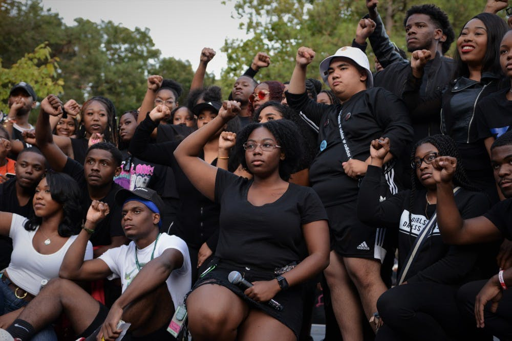 <p>Black Student Alliance MSU president Sharron Reed-Davis and others pose following her speech protesting the newly implemented block tuition at MSU during Spartan Remix behind Wells Hall on Sept. 5, 2019. Many students wore black to the event in support of the protest. </p>