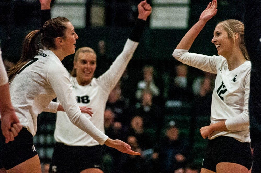 Senior middle blocker Alyssa Garvelink (17) and senior setter Rachel Minarick (12) high five after a play during the game on Nov. 1, 2017 at Jenison Fieldhouse. The Spartans fell to the Nittany Lions 3-1.