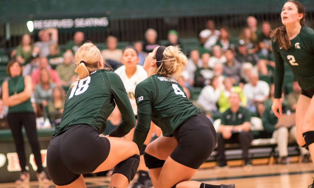 Freshman defensive specialist Jamye Cox (4) and senior outside hitter Holly Tolliver (18) go after a ball during the game against Corpus Christi. The Spartans defeated the Islanders, 3-0.