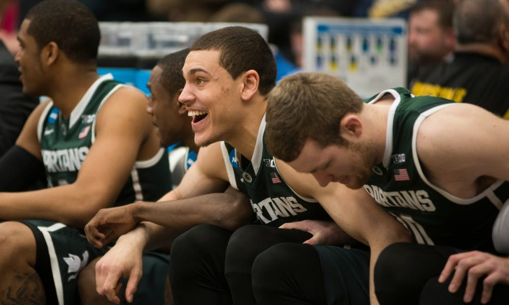 Sophomore forward Gavin Schilling and his teammates brace each other in the final seconds of the game March 29, 2015, during the East Regional round of the NCAA Tournament in the Elite Eight against Louisville at the Carrier Dome in Syracuse, New York. The Spartans defeated the Cardinals in overtime, 76-70. Erin Hampton/The State News
