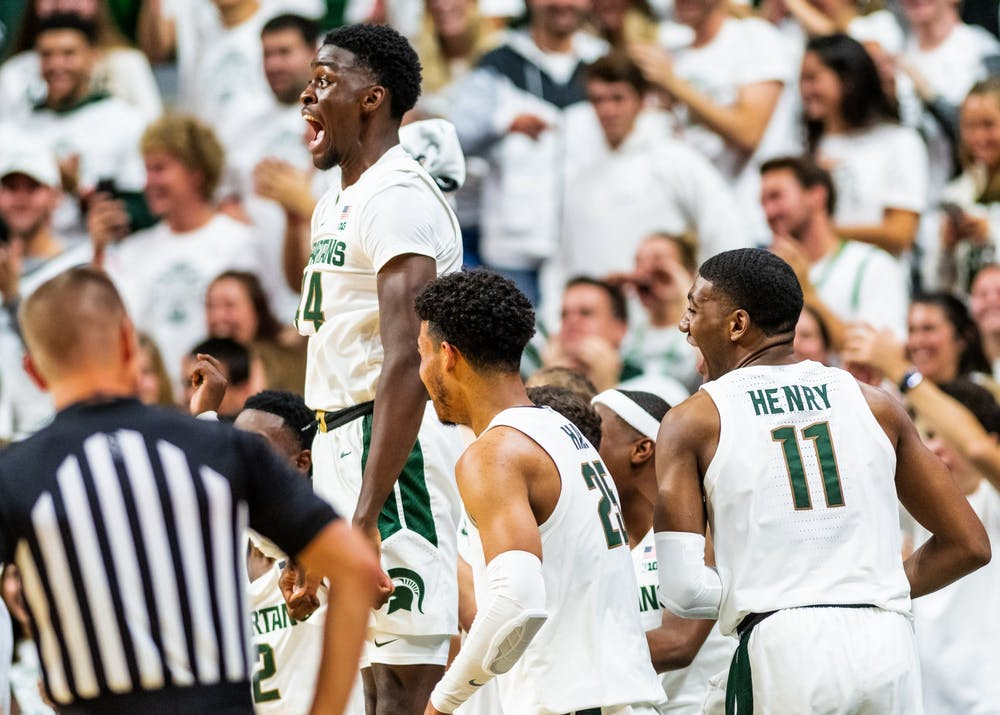 Sophomore forward Gabe Brown (left) leaps in excitement after freshman guard Steven Izzo scored his first point as a SpartanThe Spartans defeated the Britons, 85-50, at half at the Breslin Student Events Center on October 29, 2019.