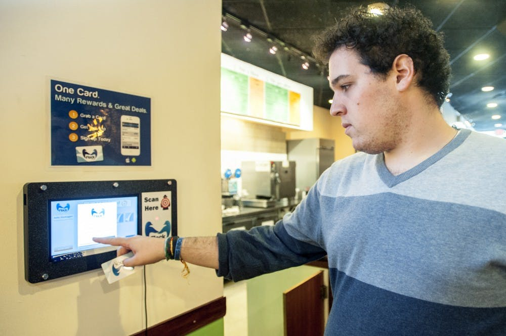Recent MSU graduate Sam Appel acticates his FlockTAG loyalty card on Thursday afternoon, Sept. 20, 2012 at Bubble Island, of 515 E. Grand River Ave. The card can be used in multiple business aross East Lansing with to collect points and rewards all within one card. Justin Wan/The State News