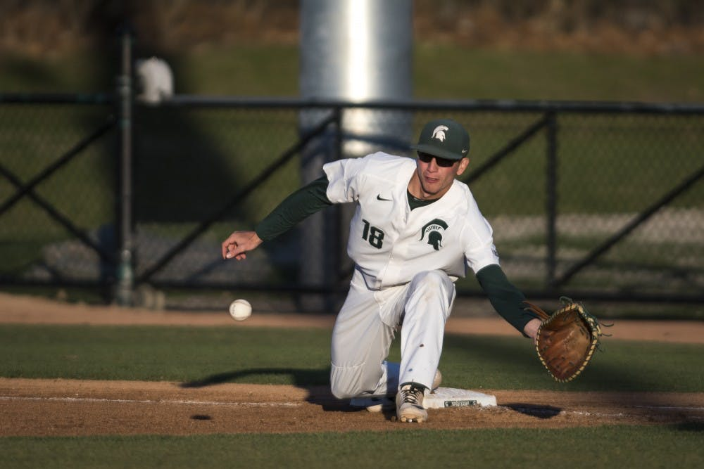 Junior infielder Justin Antoncic (18) goes to catch the ball at first base during the baseball game against Oakland University at McLane Baseball Stadium on April 23, 2019. (Nic Antaya/The State News)