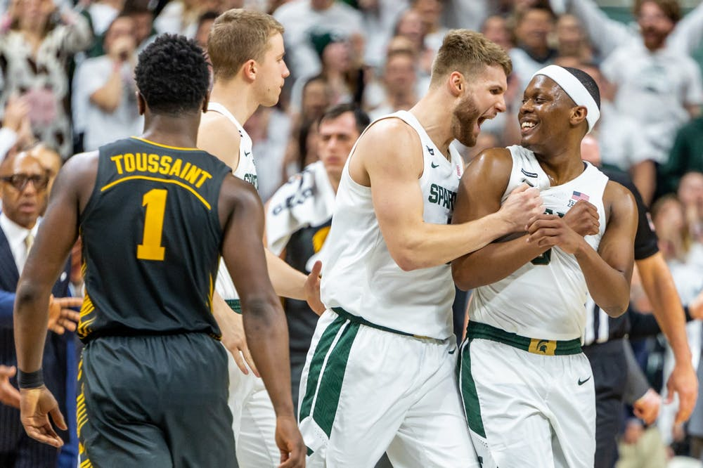 Senior forward Kyle Ahrens (left) celebrates retaking the lead with senior guard Cassius Winston (right) during a game against Iowa. The Spartans defeated the Hawkeyes, 78-70, at the Breslin Student Events Center on February 25, 2020.