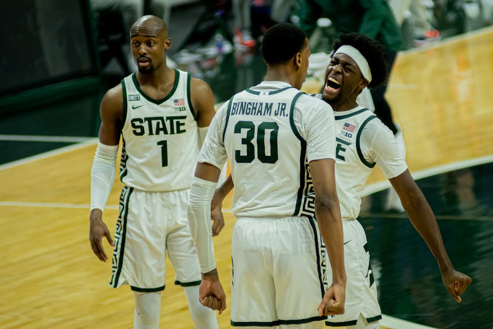 <p>Juniors Gabe Brown and Marcus Bingham Jr. celebrate a Bingham dunk and and-one opportunity against Illinois on Feb. 23, 2021. The Spartans beat the Fighting Illini, who were second in the conference, 81-72.</p>