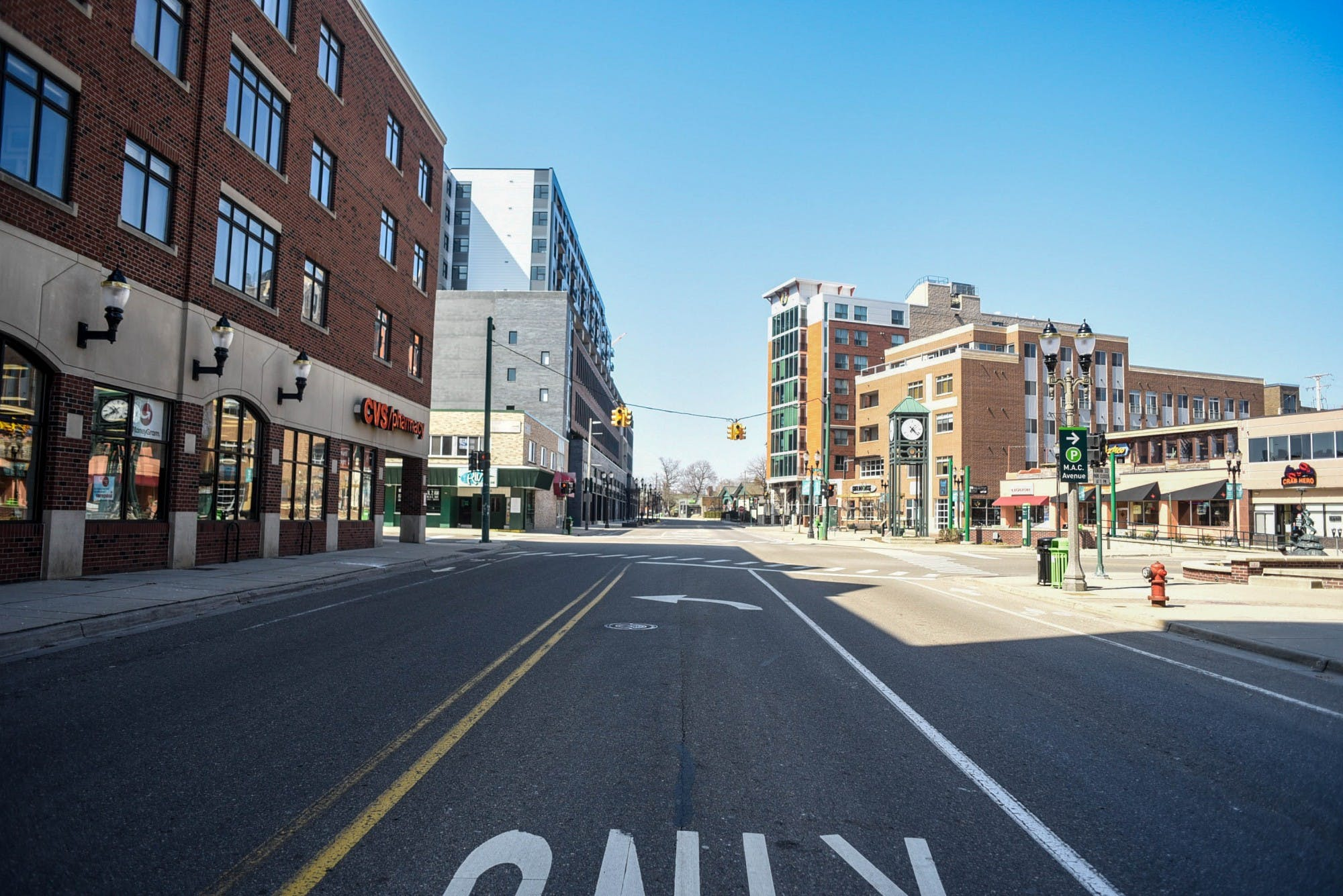 A street is empty of cars and people. On both sides of the road are tall, brick buildings. A stoplight hangs over the street's intersection.