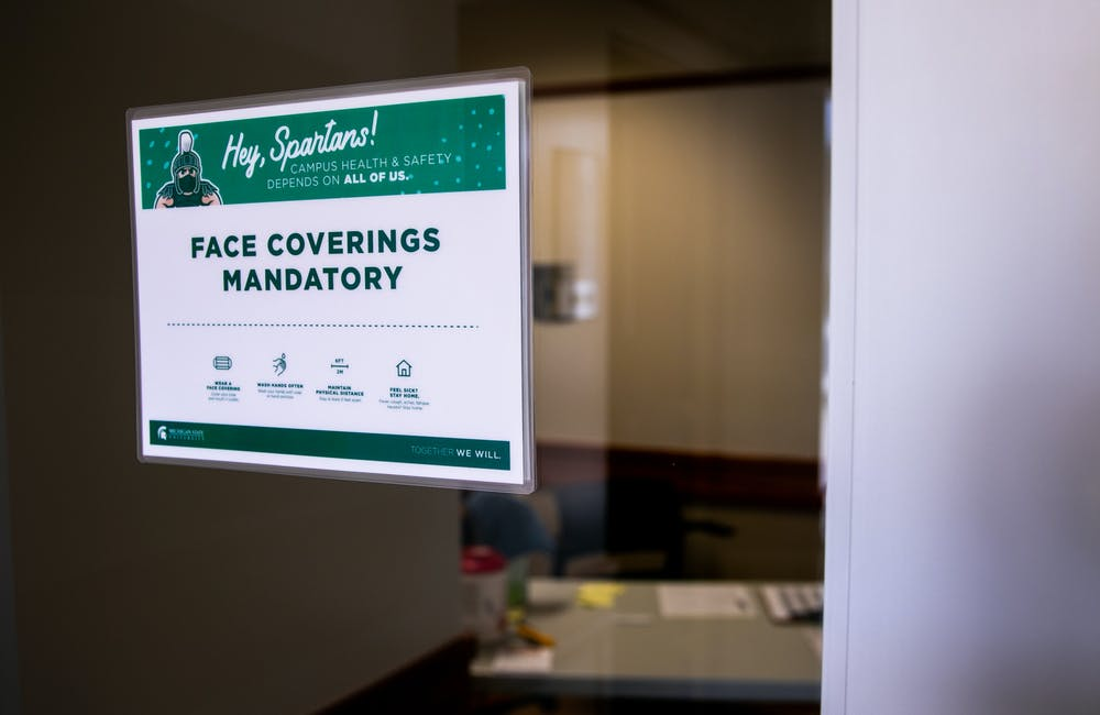A sign requiring face coverings is posted outside Olin Health Center August 24, 2020.