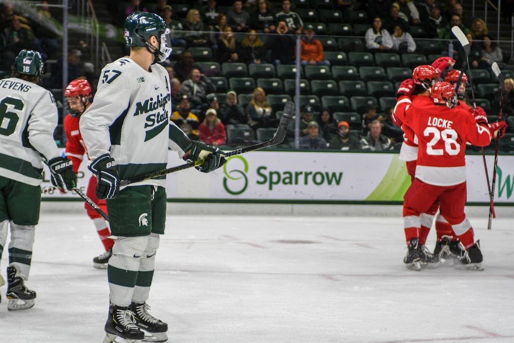 <p>Redshirt senior left defense Jerad Rosburg (57) watches as Cornell players celebrate a goal during the game against Cornell at Munn Ice Arena on Nov. 1, 2019. The Spartans fell to the Big Red, 3-2.</p>