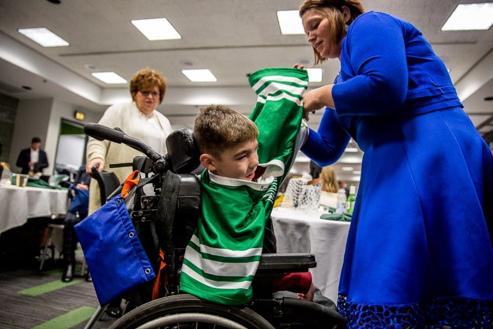 <p>Jill Willimeth helps her son Connor, 7, put a signed jersey on during the MSU Men's Lacrosse Ring Ceremony on Dec. 1, 2018 at the Breslin Center.</p>