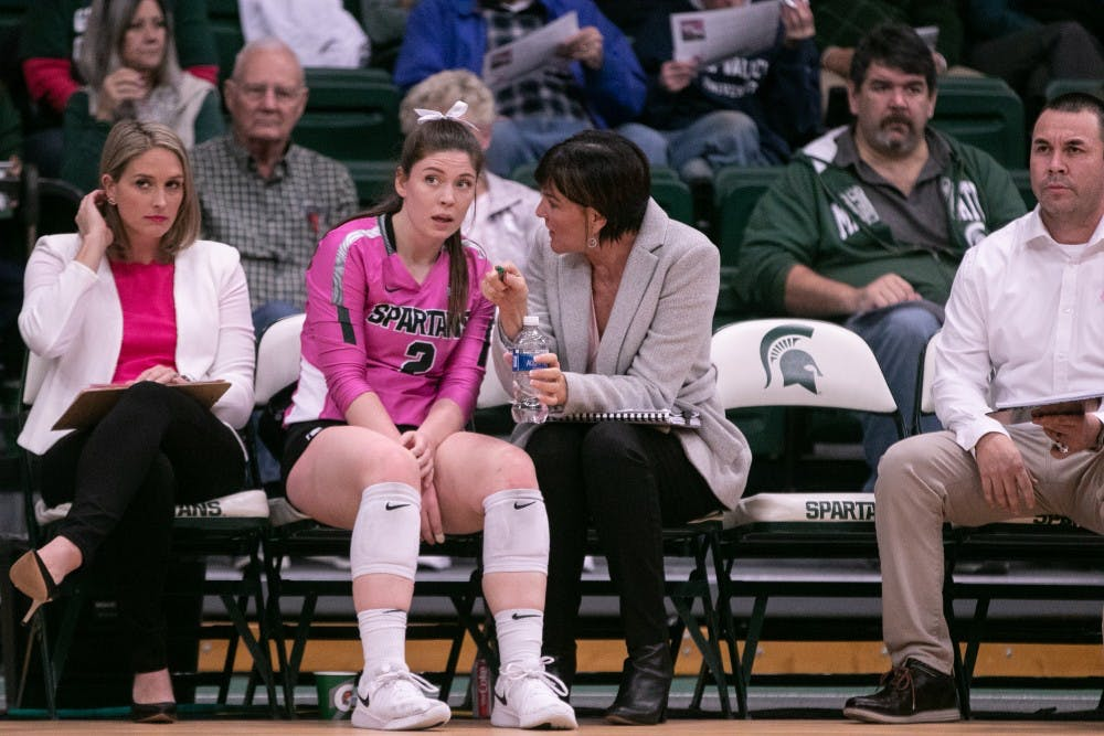 <p>Graduate setter Audrey Alford (2) listens to Head Coach Cathy George during their game against Wisconsin on Oct. 25, 2019, at Jenison Fieldhouse. The Spartans fell to the Badgers, 0-3.</p>