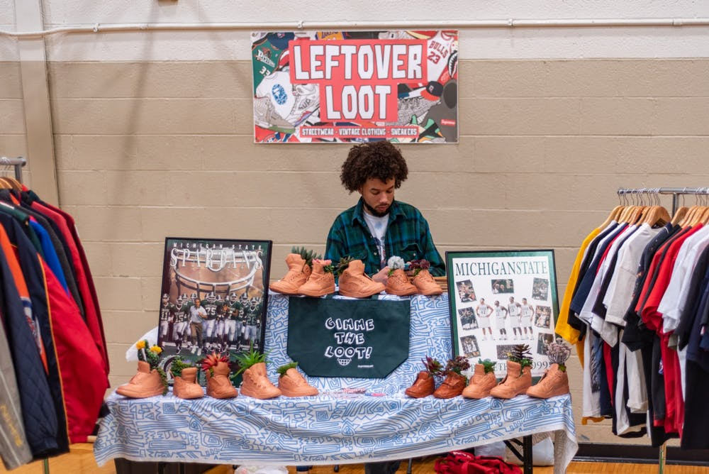 <p>A seller waits at his booth, decorated with sneaker-shaped plant pots at the Sparta-Kickz convention at IM Sports West on Feb. 23, 2020. </p>