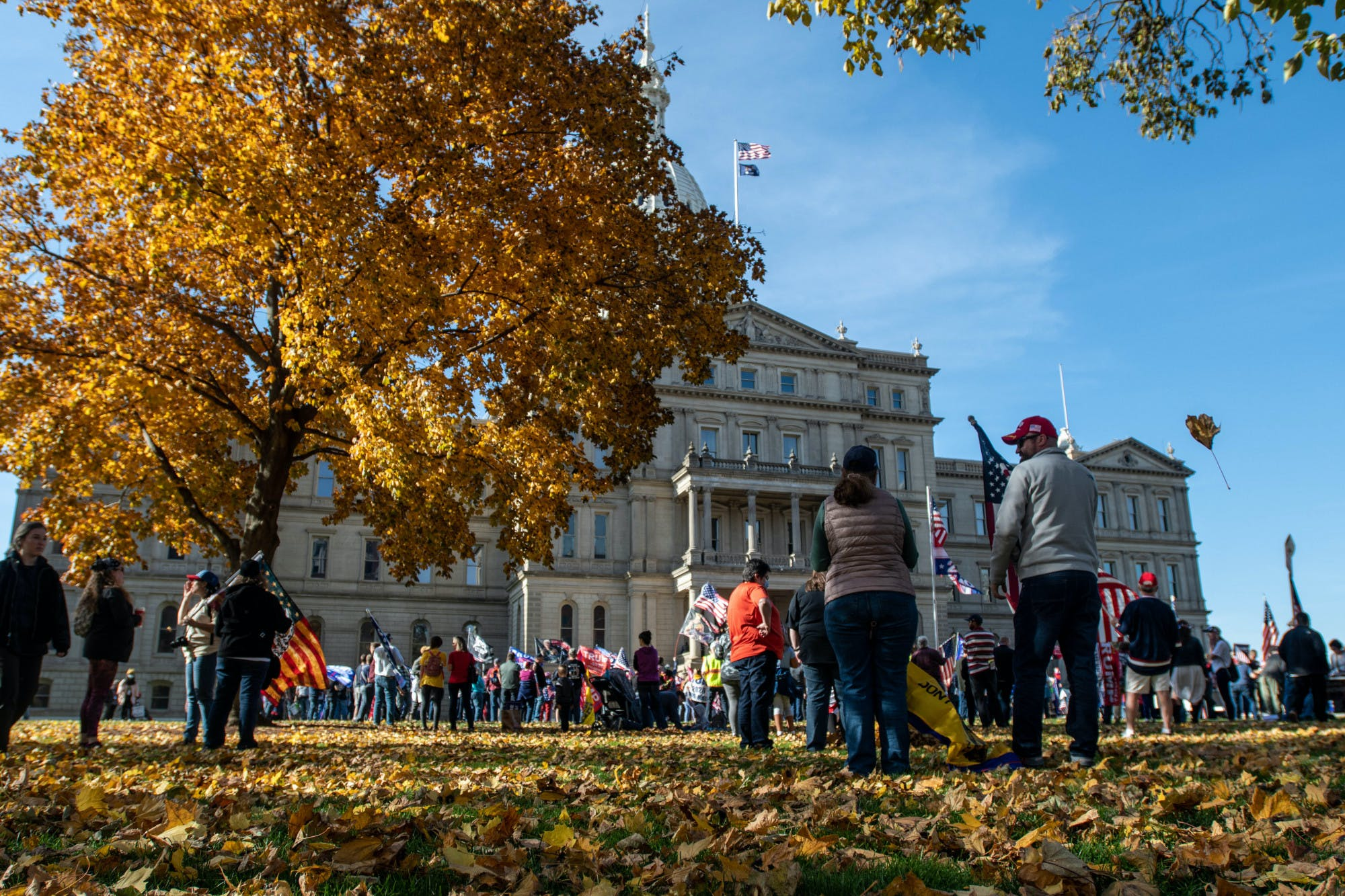 A crowd of people gather at the Michigan State Capitol.