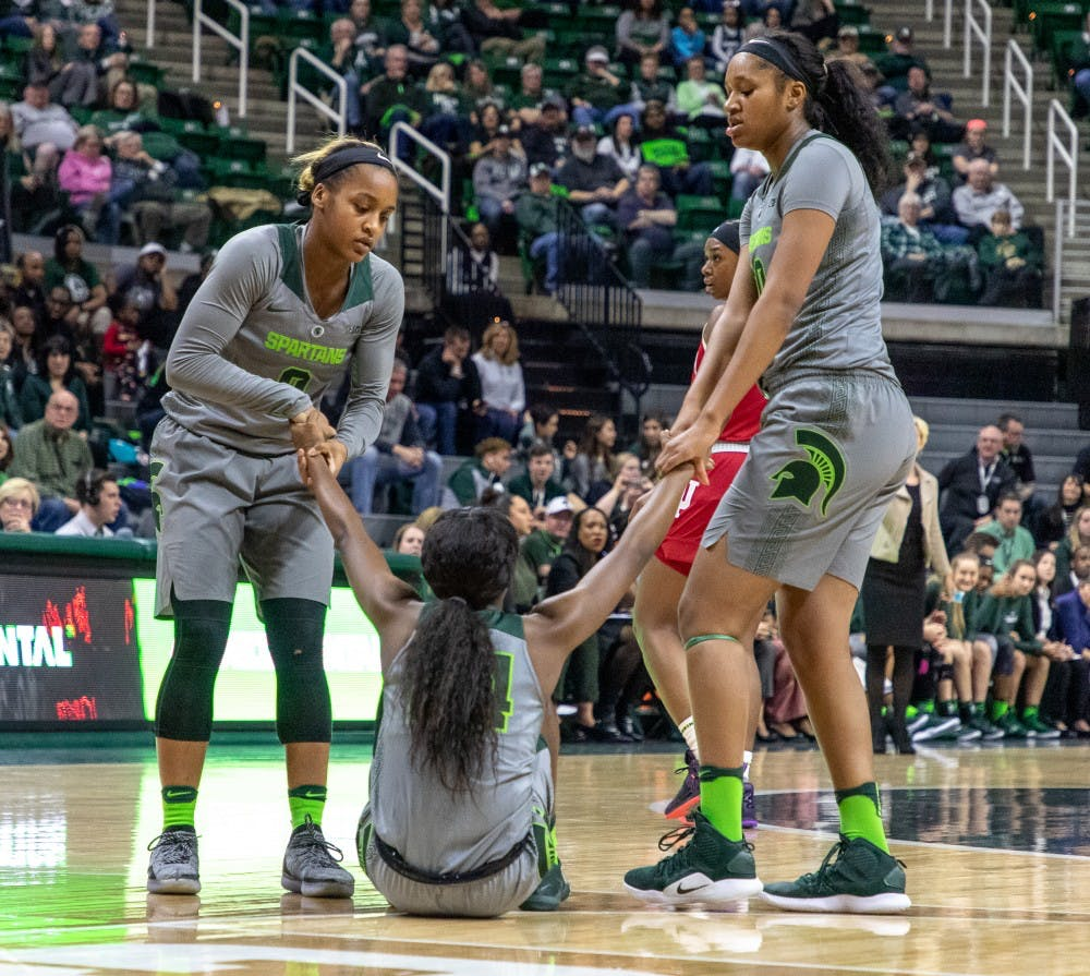 Redshirt junior guard Shay Colley (0) and Freshman forward Sidney Cooks (10) help up Freshman guard Nia Clouden (24) during the game against Indiana on Feb.11, 2019. The Spartans lead the Hoosiers 33-30 at halftime.