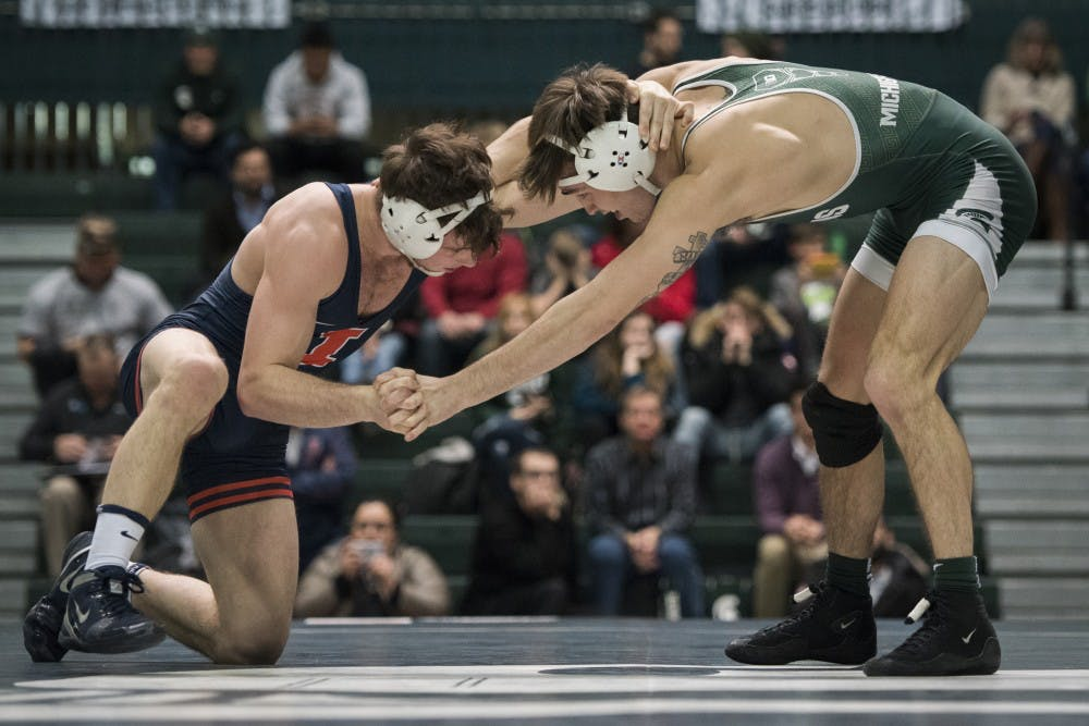 Redshirt sophomore 157-pounder Jake Tucker and Illinois' Eric Barone wrestle during a match on Jan. 11, 2019 at Jenison Field House. Tucker lost the match. Nic Antaya/The State News