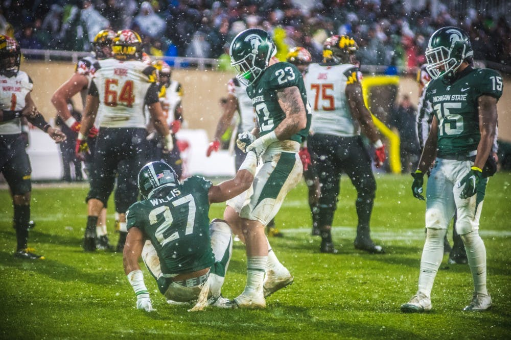 Senior linebacker Chris Frey (23) helps up junior safety Khari Willis (27) during the game against Maryland on Nov. 18, 2017, at Spartan Stadium. The Spartans defeated the Terrapins, 17-7.
