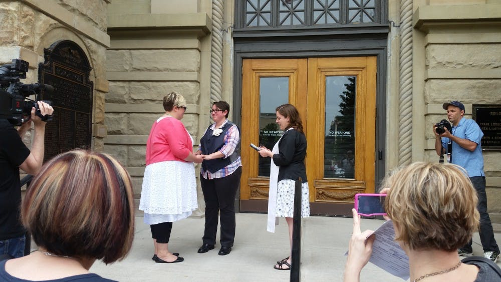 <p>Rev. Nicolette Siragusa officiates a same-sexmarriage on the steps of the Ingham County Clerk's office on Friday, June 26, 2015.</p>