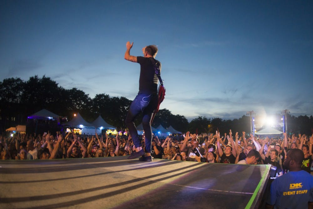 <p>Tim McIlrath of Rise Against encourages the crowed to clap during Common Ground Music Festival on July 6, 2016 at Adado Riverfront Park in Lansing. McIlrath has been rhythm guitar for Rise Against since 1999.</p>