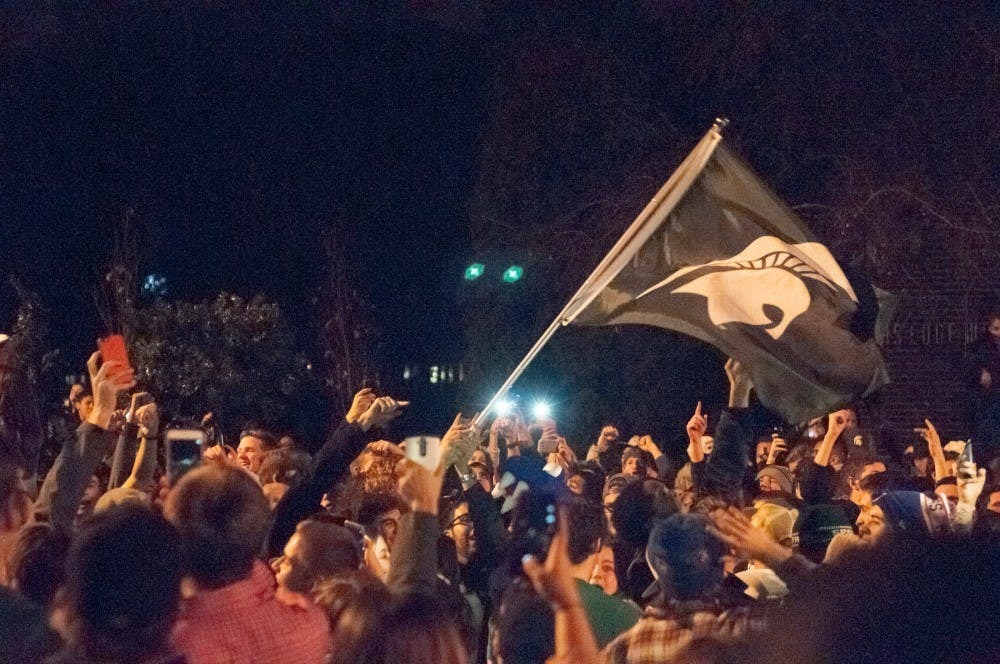 Students celebrate on the street after MSU's victory over Iowa on Dec. 5th, 2015, at Cedar Village.