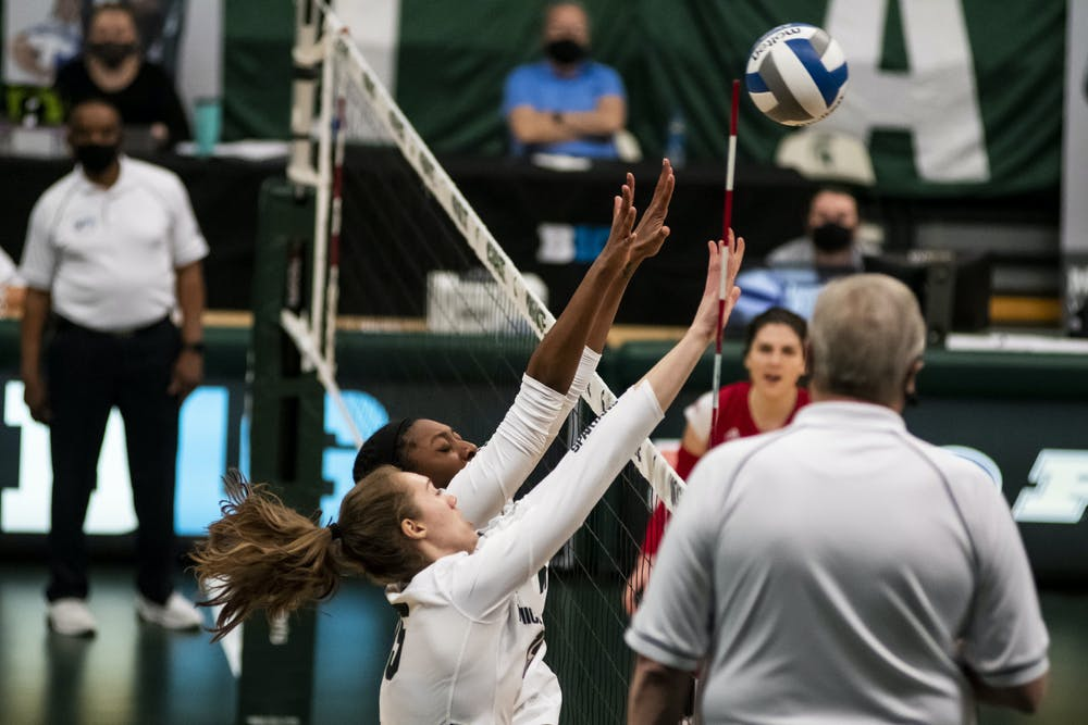 <p>Then-redshirt senior outside hitter Lauren Swartz (15) and junior middle blocker Naya Gros (17) blocking the ball at the net during the game against Rutgers on April 2, 2021, at the Jenison Fieldhouse. The Scarlet Knights defeated the Spartans 3-2.</p>