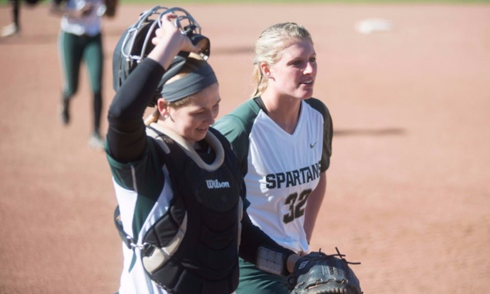 <p>Sophomore Bridgette Rainey, right, and sophomore catcher Jordan Davis walk to the dugout during the game against Broncos on March 29, 2016 at Secchia Softball Stadium. The Spartans defeated the Western Broncos, 12-2.</p>