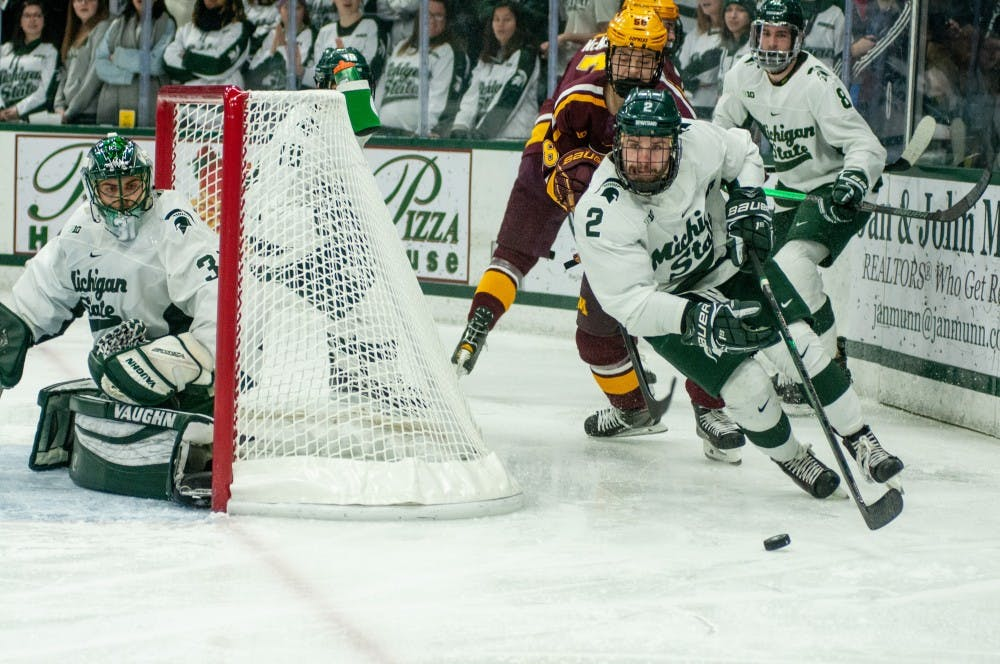 Senior right defense Zach Osburn (2) cuts around the goal during the game against Minnesota on Jan. 19, 2019 at Munn Ice Arena. The Spartans defeated the Gophers, 5-3.