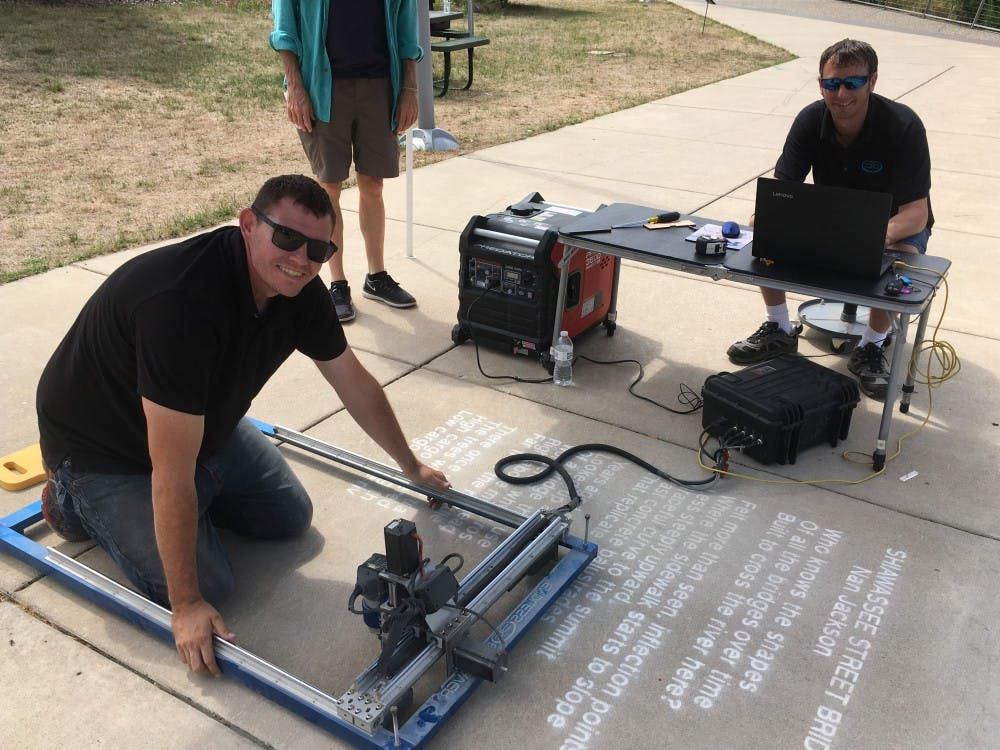<p>Don Easlick and Ralph Hansel of Endless Engravings in Charlotte, Michigan, etch a contest-winning poem into a Lansing sidewalk. <strong>Photo courtesy of Ruelaine Stokes.</strong></p>