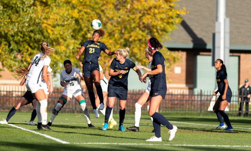 <p>Michigan defender Sydney Shepherd (21) clears a corner kick against Michigan State. The Wolverines defeated the Spartans at DeMartin Soccer Stadium, 3-2, on Oct. 19, 2019. </p>