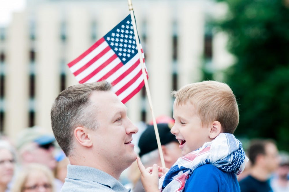 President of the Michigan Open Carry Tom Lambert holds his son William Lambert, 4, at the Second Amendment March at the Michigan State Capitol on June 20, 2018.
