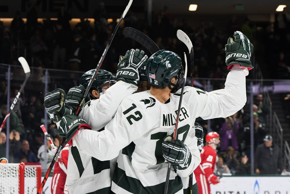 Players celebrate a goal by forward Tommy Miller (12) during the game against Wisconsin at the Munn Ice Arena on December 6, 2019. The Spartans defeated the Badgers 3-0.