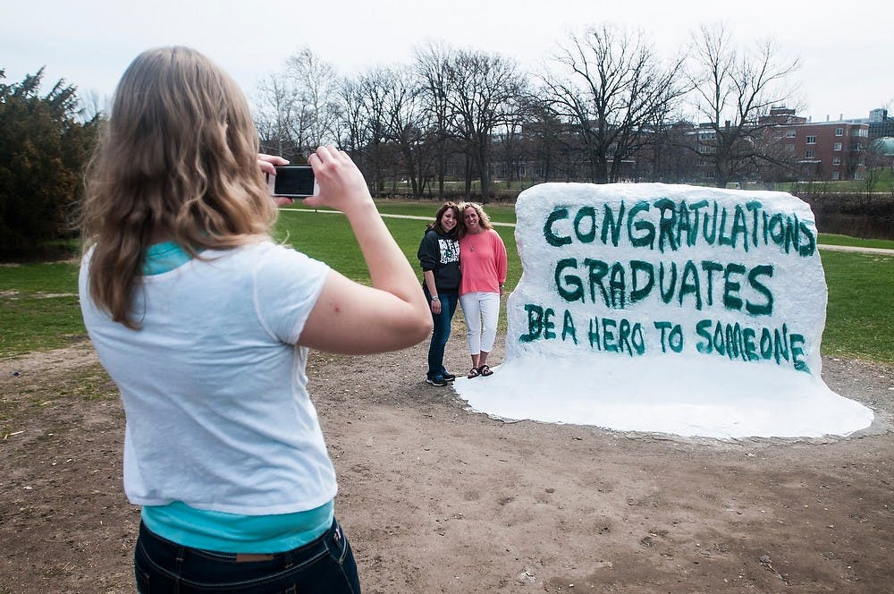 <p>Graduate student Kelsey Lehman takes a photo of graduate students Deanna Burbank, left, and Deanna Swan on April 21, 2014, at the Rock on Farm Lane. The Rock was previously painted in memory of Lacey Holsworth with messages from Spartans on it. Erin Hampton/The State News</p>