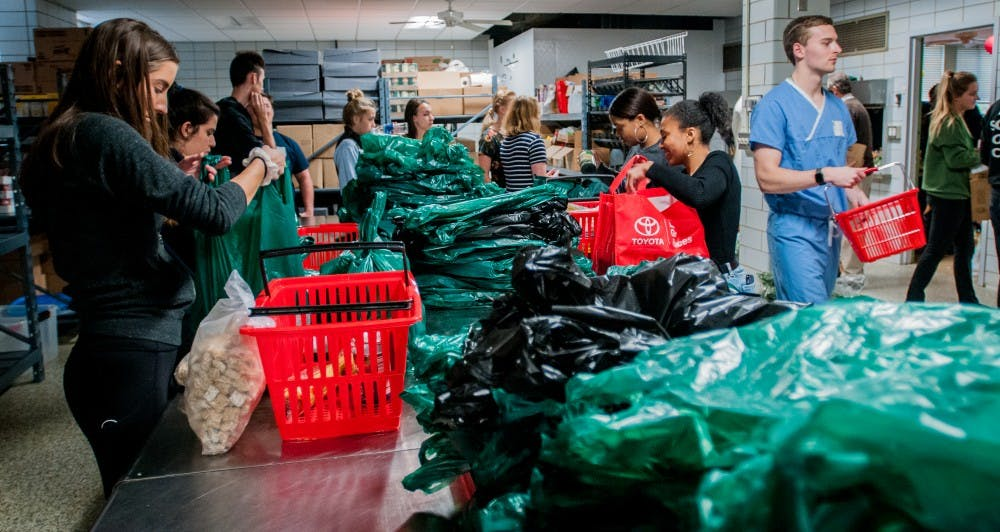 <p>Volunteers work together to transfer food from shopping baskets to shopping bags to be distributed out for the MSU Food Bank Oct. 17, 2018 at Olin Heath Center.</p>