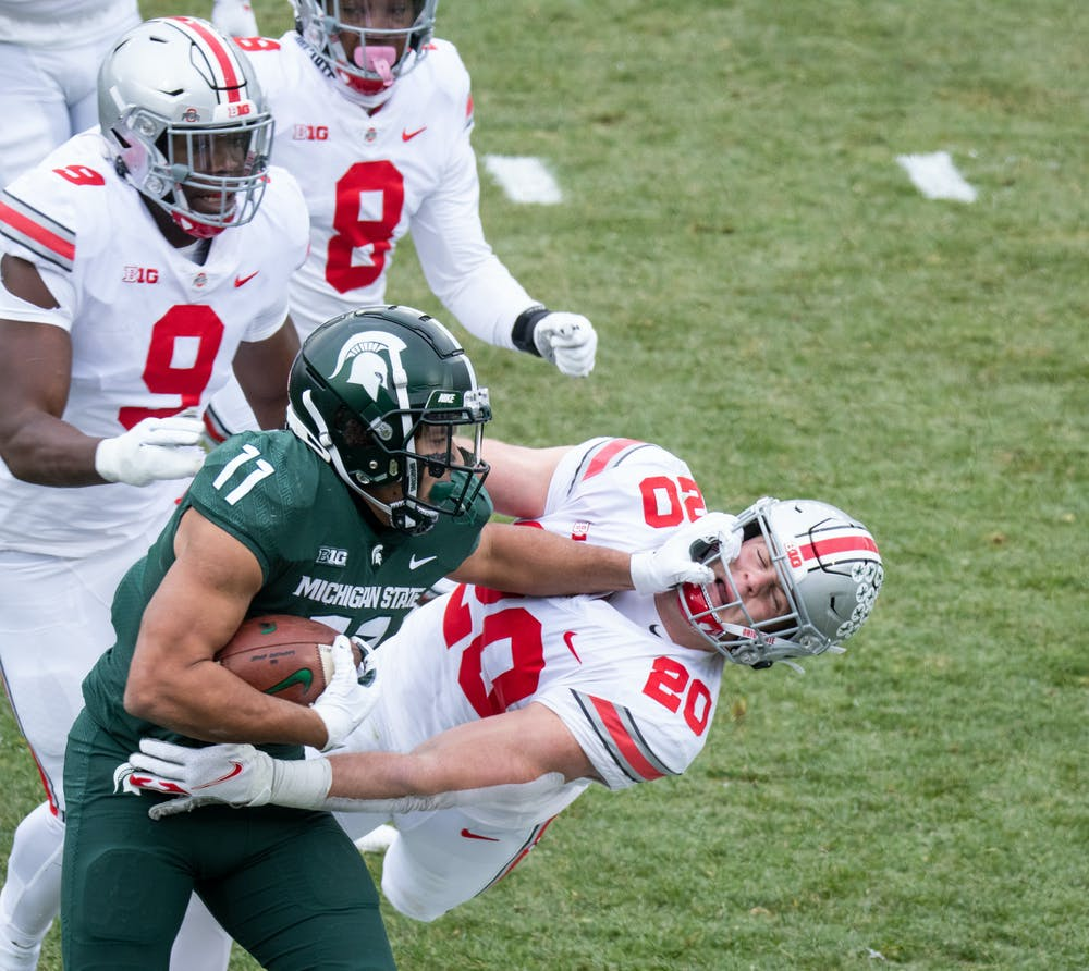 MSU runningback, Connor Heyward (11), carries the ball for Michigan State in a game against OSU in Spartan Stadium on Dec. 5, 2020.