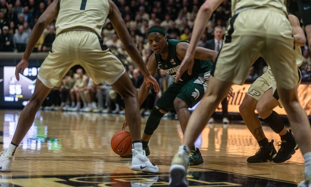 <p>Guard Cassius Winston (5) peers through Purdue's defense on Jan. 27, 2019 at Mackey Arena. The Spartans fell to the Boilermakers, 73-63.</p>