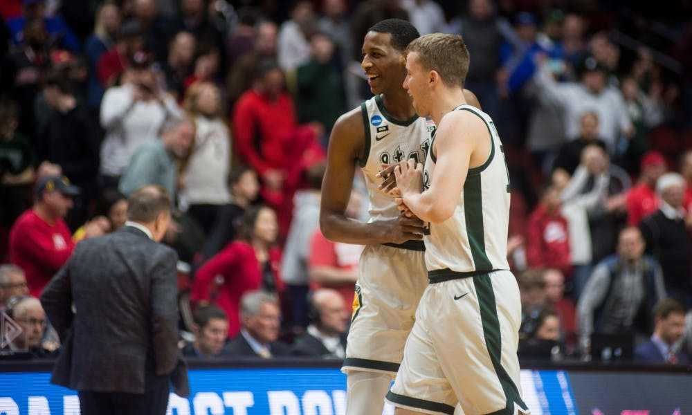 <p>Freshmen forwards Marcus Bingham Jr. (30) and Thomas Kithier (15) celebrate their win after the NCAA tournament game against Bradley at Wells Fargo Arena on March 21, 2019. The Spartans defeated the Braves, 76-65.</p>