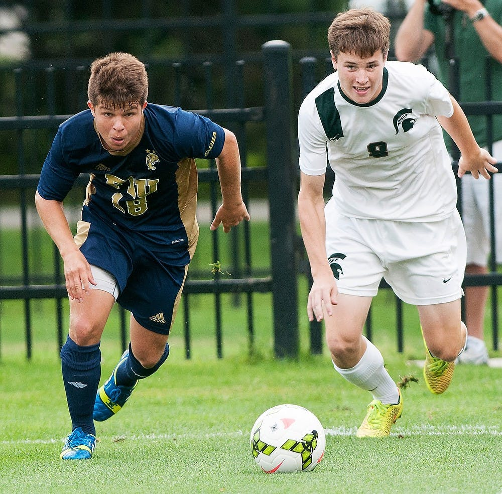 <p>Freshman midfielder Michael Marcantognini charges toward the ball alongside Florida International defender Juan Benedetty on Aug. 31, 2014, at DeMartin Soccer Stadium at Old College Field. The Spartans defeated the Panthers, 3-0. Raymond Williams/The State News</p>