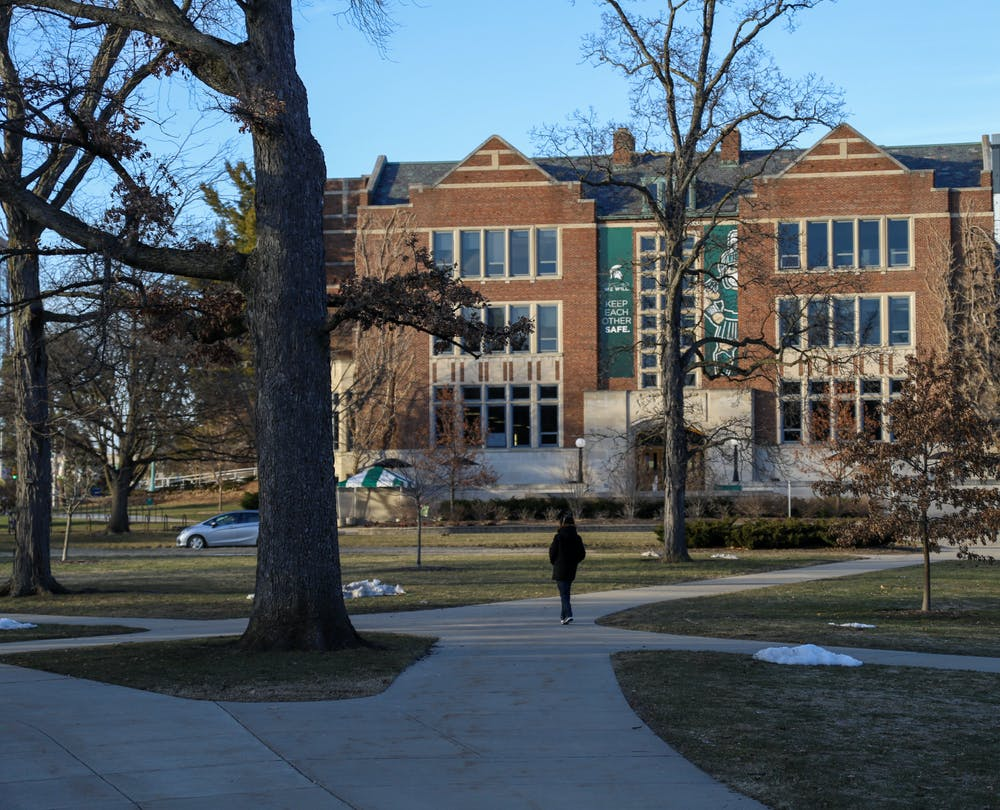 <p>The MSU Union has a large sign that says, &quot;Keep Each Other Safe,&quot; and below the sign is a person walking on campus on March 7, 2021. </p>