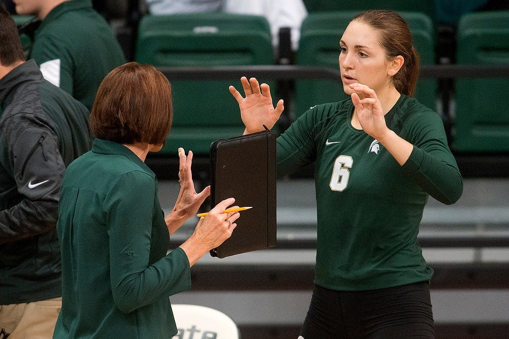 <p>Head coach Cathy George talks to then sophomore middle blocker/opposite Allyssah Fitterer during a timeout during a game against LIU Brooklyn on Sept. 19, 2014, at Jenison Field House. The Spartans lost, 3-2. Julia Nagy/The State News</p>