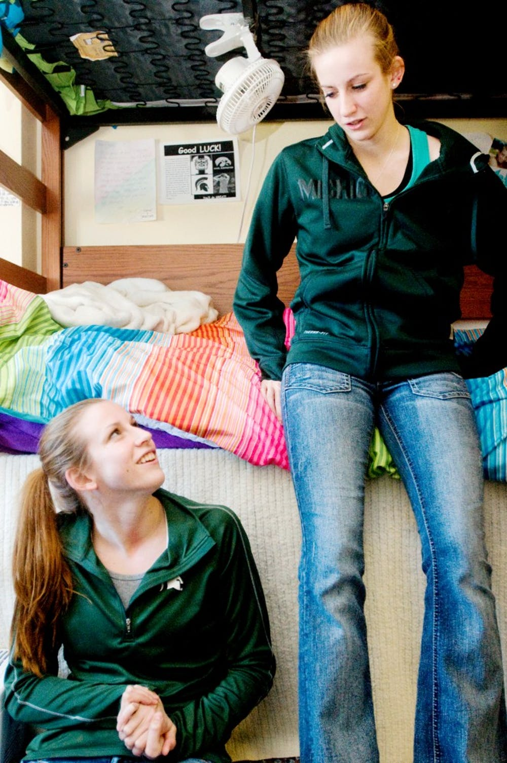 Sophomore dietetics student Erica Cultler, left, and her twin sister sophomore elementary education student Jessica Cutler, right, talk in their dorm room Thursday in Wonders Hall. The twins are on the swimming and diving team at MSU. Jaclyn McNeal/The State News