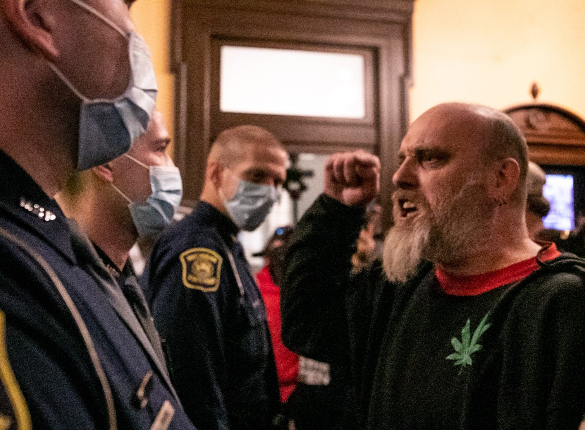 A person without a mask wearing a shirt with a marijuana leaf points at police officers wearing masks.