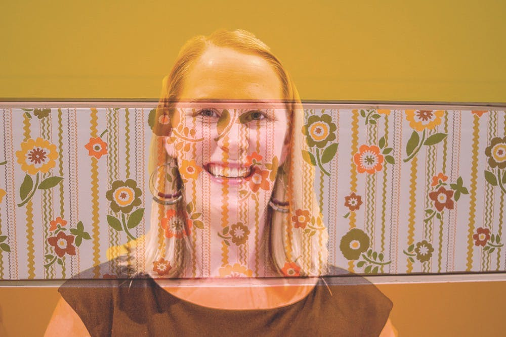 <p>Studio art masters student Laura Baszynski poses for a portrait in this double exposure, with her artwork at the MFA Broad Exhibition reception on April 7, 2018 at the Broad Art Museum.&nbsp;</p>
