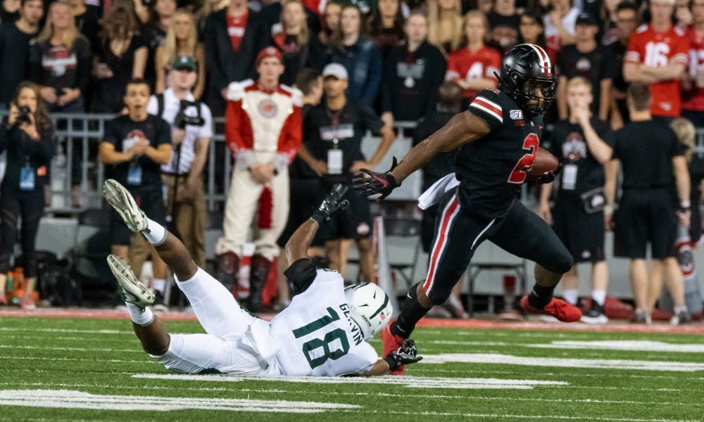 <p>Ohio state running back J.K. Dobbins (2) evades freshman cornerback Kalon Gervin (18). The Buckeyes defeated the Spartans, 34-10, at Ohio Stadium on Oct. 5, 2019. </p>