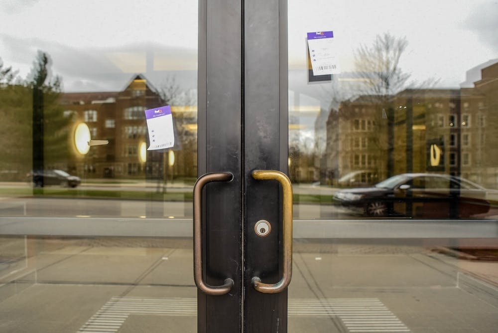 Fed Ex missed packages notices on a door in downtown East Lansing on April 1, 2020.