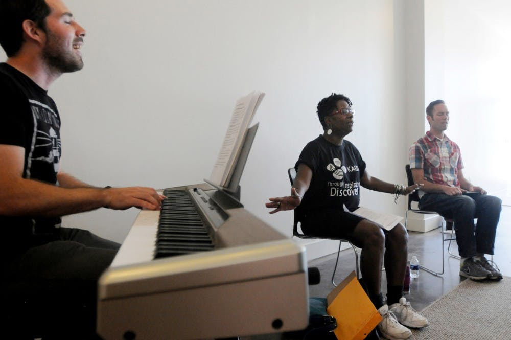 <p>Lansing resident Justin Reid plays the piano while Lansing residents Irene Unkefer and Jessie Still sing during a prayer circle Sept. 16, 2015 at The Furnace, 619 E. Grand River Ave., in East Lansing.</p>
