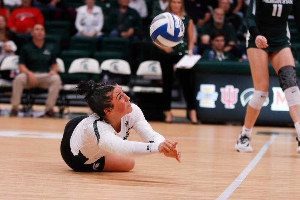 <p>Junior libero Jayme Cox (4) dives for a ball during the game against Cincinnati on Sept. 6, 2019 at Jenison Fieldhouse. The Spartans defeated the Bearcats, 3-1.</p>