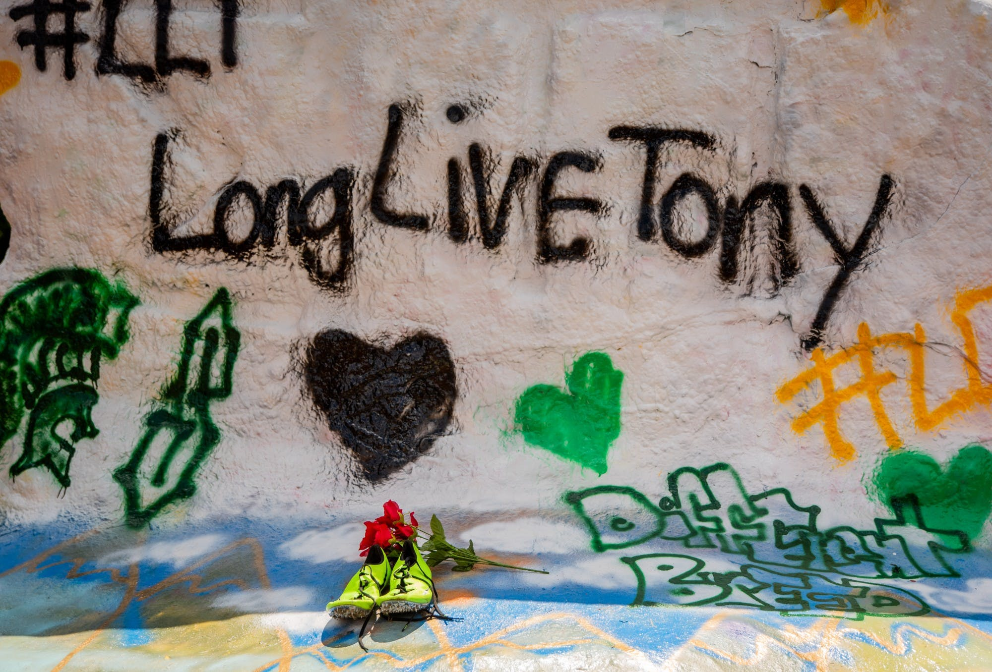 A pair of running shoes and red flowers sit in front of a painted rock that reads 'Long live Tony.'